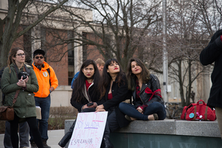 Three SU students sit together. All three spoke at the rally, calling for unity against aggressive immigration enforcement tactics.