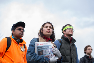Students somberly listen to speakers at the rally. One student holds a newspaper related to socialism.
